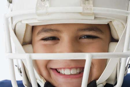 Close up of Hispanic boy wearing football helmet