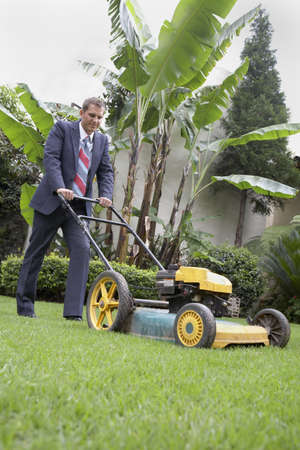 Hispanic businessman pushing lawn mower