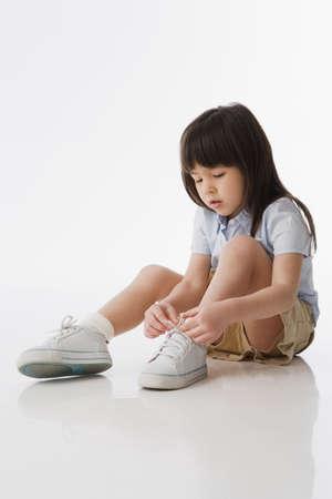 Asian girl tying shoelaces