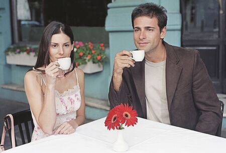 Hispanic couple drinking coffee at outdoor cafe