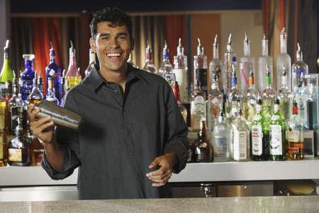 Hispanic male bartender making drink LANG_EVOIMAGES