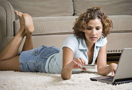 Hispanic woman laying on floor with laptop and credit card