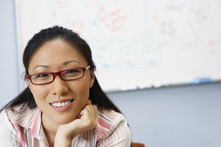 Portrait of Asian businesswoman in front of whiteboard LANG_EVOIMAGES