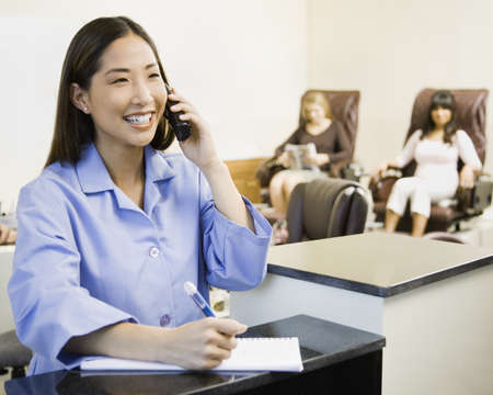 Asian nail technician talking on telephone LANG_EVOIMAGES