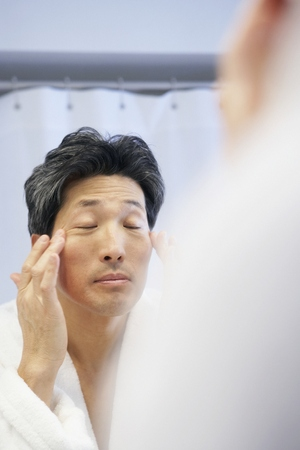 Asian man rubbing face in mirror LANG_EVOIMAGES