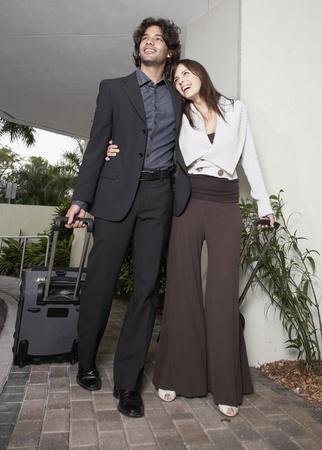 Hispanic couple walking with suitcase