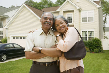 Senior African couple in front of house