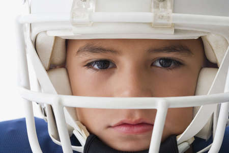Close up of Hispanic boy wearing football helmet