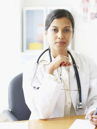 Indian female doctor sitting at desk LANG_EVOIMAGES