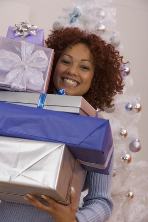 African woman carrying stack of Christmas gifts