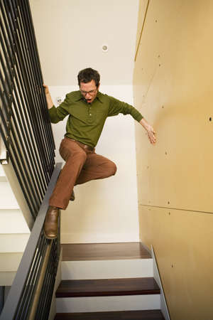Young man sliding down banister on feet LANG_EVOIMAGES