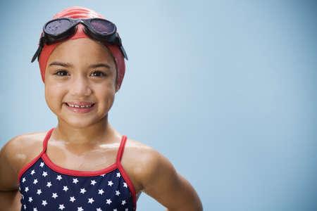 Hispánská dívka v plavkách s brýlemi a plaveckou čepicí