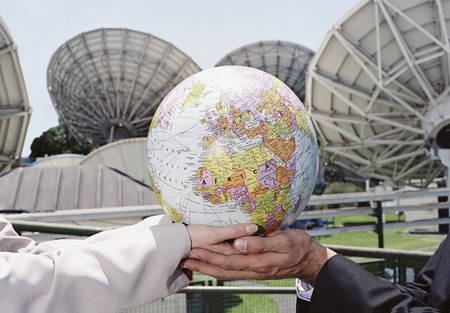 Businesspeople holding globe in front of satellite dishes
