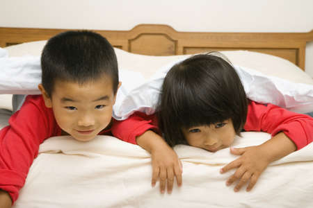 Asian brother and sister laying on bed LANG_EVOIMAGES