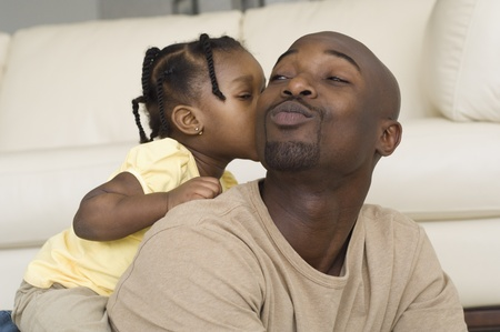 African girl kissing father's cheek
