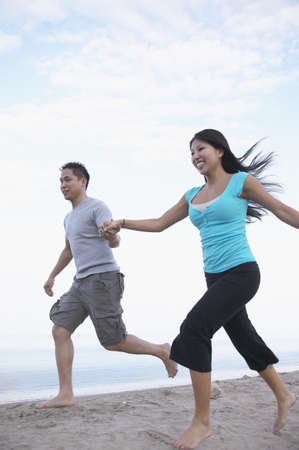 Asian couple holding hands and running at beach
