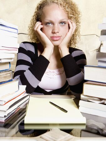Young woman studying at desk with large stacks of books and notepad