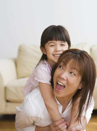 Asian mother giving daughter piggy back ride