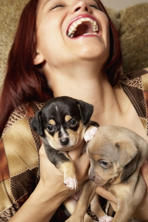 Hispanic woman holding puppies LANG_EVOIMAGES