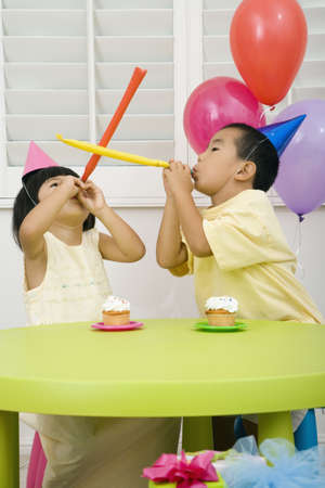 Asian brother and sister at birthday party