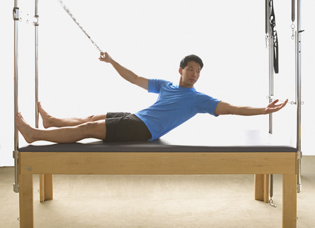 Asian man stretching on exercise equipment LANG_EVOIMAGES