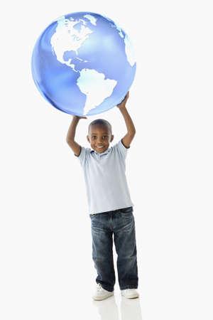 African American boy holding globe over head