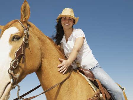Hispanic woman riding horse LANG_EVOIMAGES
