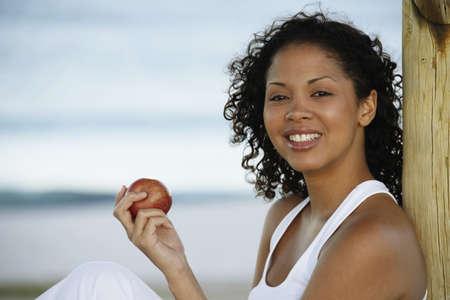 Mixed Race woman eating apple