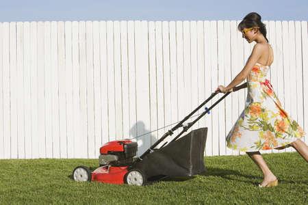 Hispanic woman in dress pushing lawn mower LANG_EVOIMAGES