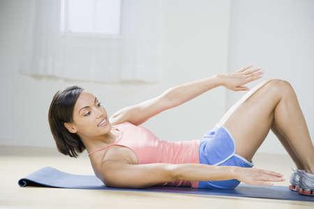 African American woman exercising on yoga mat