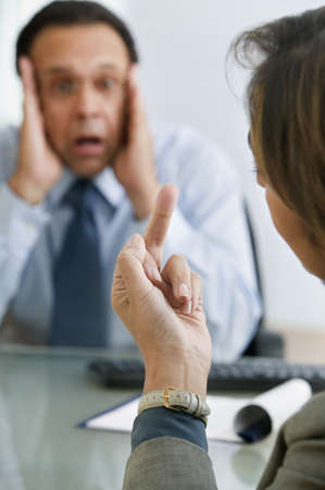 Businesswoman giving middle finger to businessman  LANG_EVOIMAGES