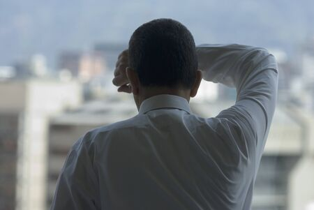 Hispanic businessman looking out window LANG_EVOIMAGES