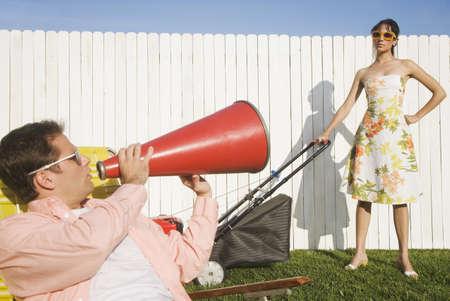 Man yelling at wife pushing lawn mower