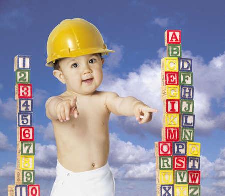 Asian baby wearing hard hat next to blocks LANG_EVOIMAGES