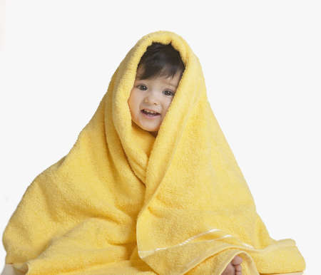 Studio shot of Hispanic baby wrapped in towel LANG_EVOIMAGES