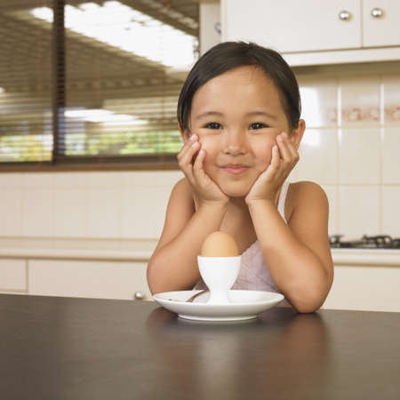 Asian girl with egg in cup