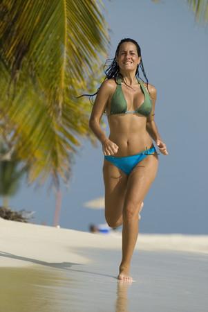 Hispanic woman jogging on beach