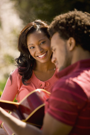 African American man playing guitar for girlfriend