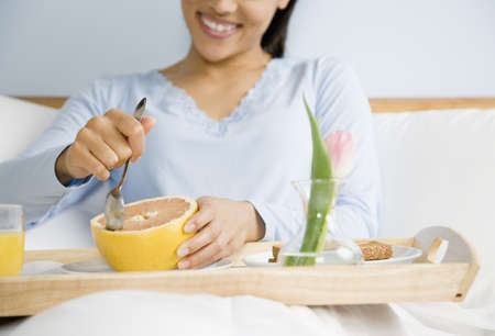 African American woman eating breakfast in bed LANG_EVOIMAGES