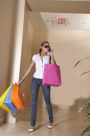 Hispanic woman carrying shopping bags LANG_EVOIMAGES