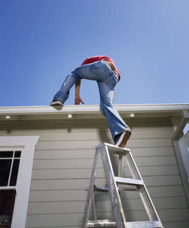 Hispanic man climbing on to roof