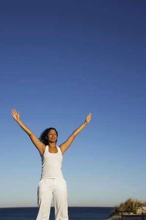 Mujer de raza mixta con los brazos alzados