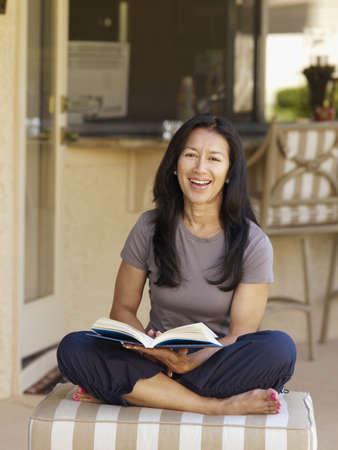 Eurasian woman reading book