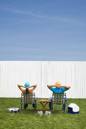 Multi-ethnic couple looking at newly painted fence