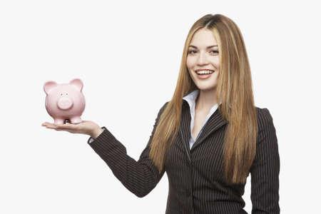 Hispanic businesswoman holding piggy bank