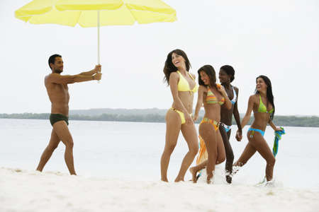 South American man holding umbrella for women at beach