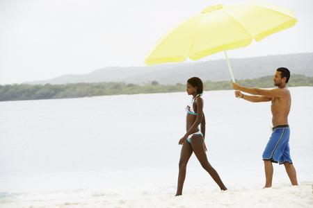 Hombre sudamericano con paraguas para mujer en la playa