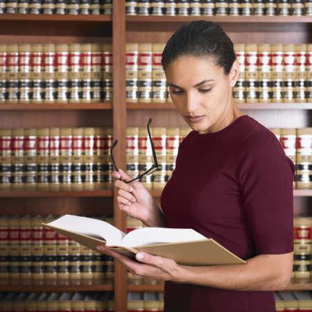 Hispanic female lawyer reading LANG_EVOIMAGES