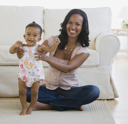 African American mother helping baby stand LANG_EVOIMAGES