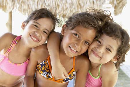 Hispanic girls hugging LANG_EVOIMAGES